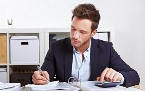 Mann sitzt mit Taschenrechner und Akten im Büro am Schreibtisch