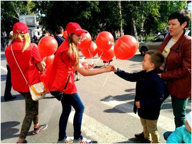 Промоутер раздает шарики с логотипом на улице